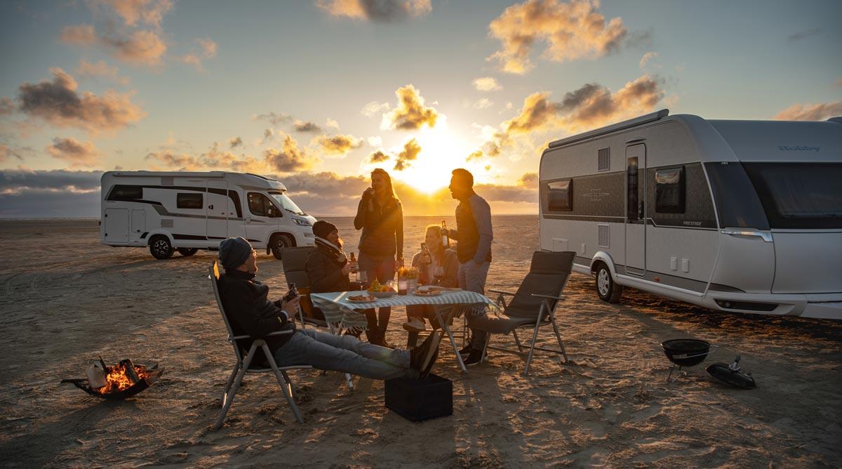 Bobil og campingvogn på strand. Flere mennesker sitter og står rundt et campingbord. Solnedgang.