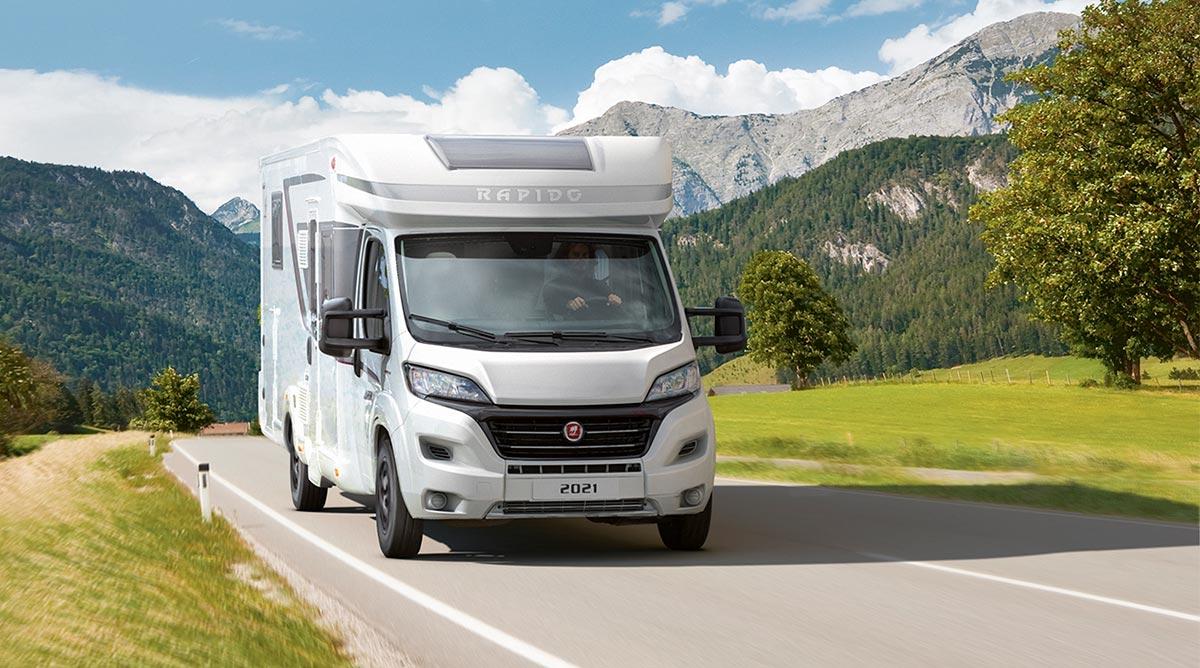 Rapido bobil 2021-modell kjører i landskap med mye fjell rund. Sommersdag og solfylt.